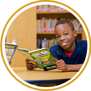 Boy smiling while holding a book